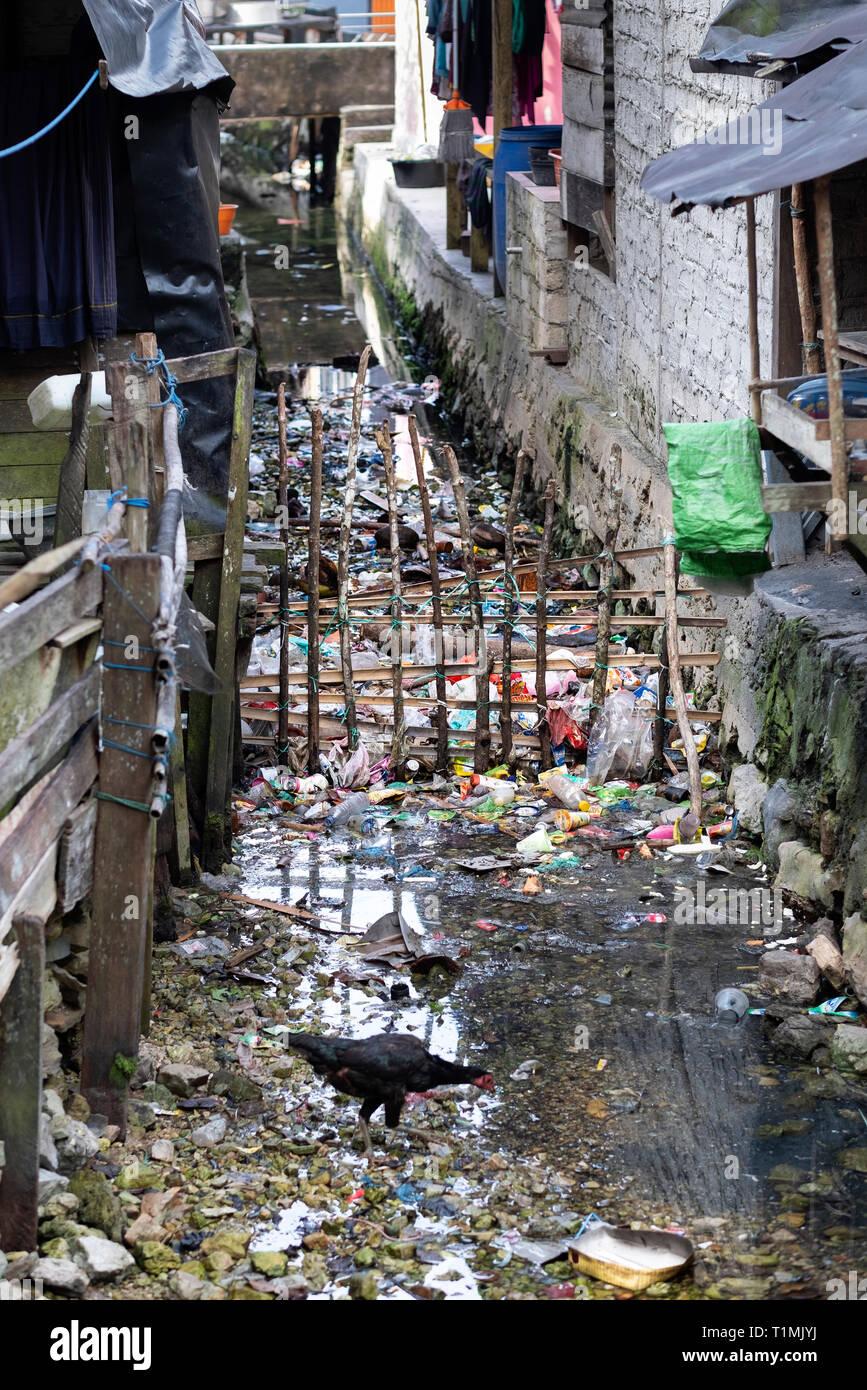 Müll und entsorgt Abfälle aus Kunststoffen in einer Wasserstraße in einem kleinen Fischerdorf auf der Insel Seram, Indonesien Stockbild
