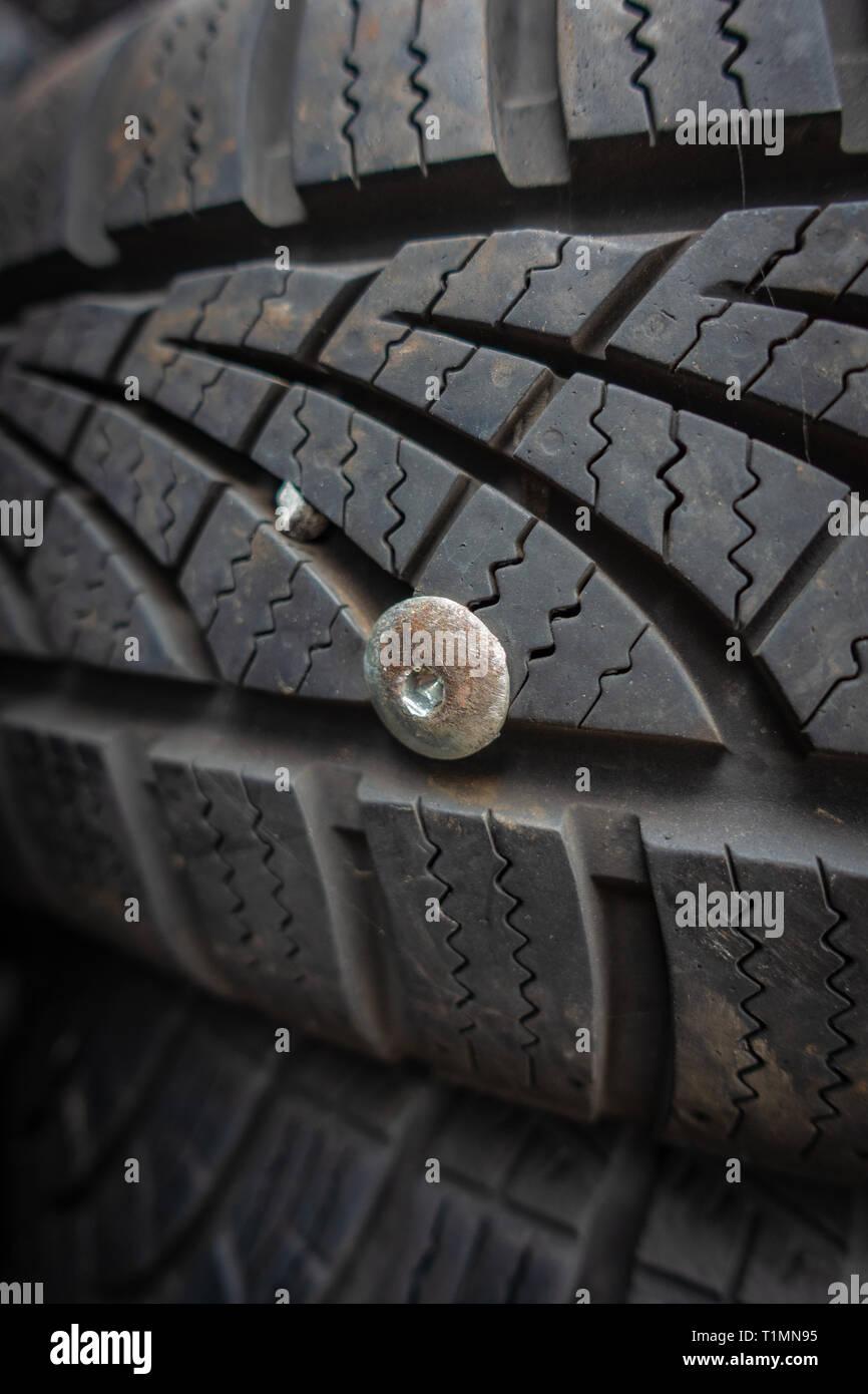 Nahaufnahme eines verwendet und nutzlos Auto Reifen durchstochen mit metall nieten Stockbild