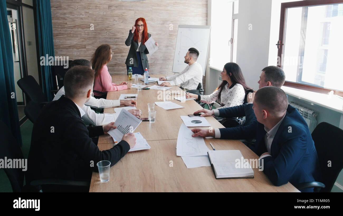 Die Leute an der Konferenz. Verärgert Frau Chef schimpft an Ihre Kollegen Stockbild