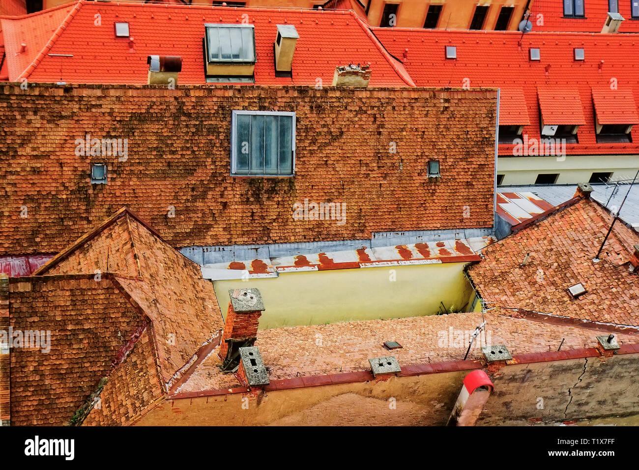 Alte Häuser mit Fliesen- grosses harmonisch ineinander über die Dächer der Häuser von neuen Gebäuden. Das Konzept der Alten und Neuen in der Architektur. Ansicht von oben Stockbild