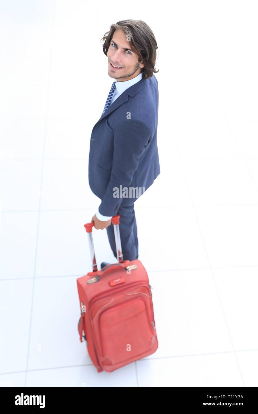 Ansicht von oben und hinten. Geschäftsmann mit Reisekoffer erlischt. Stockbild