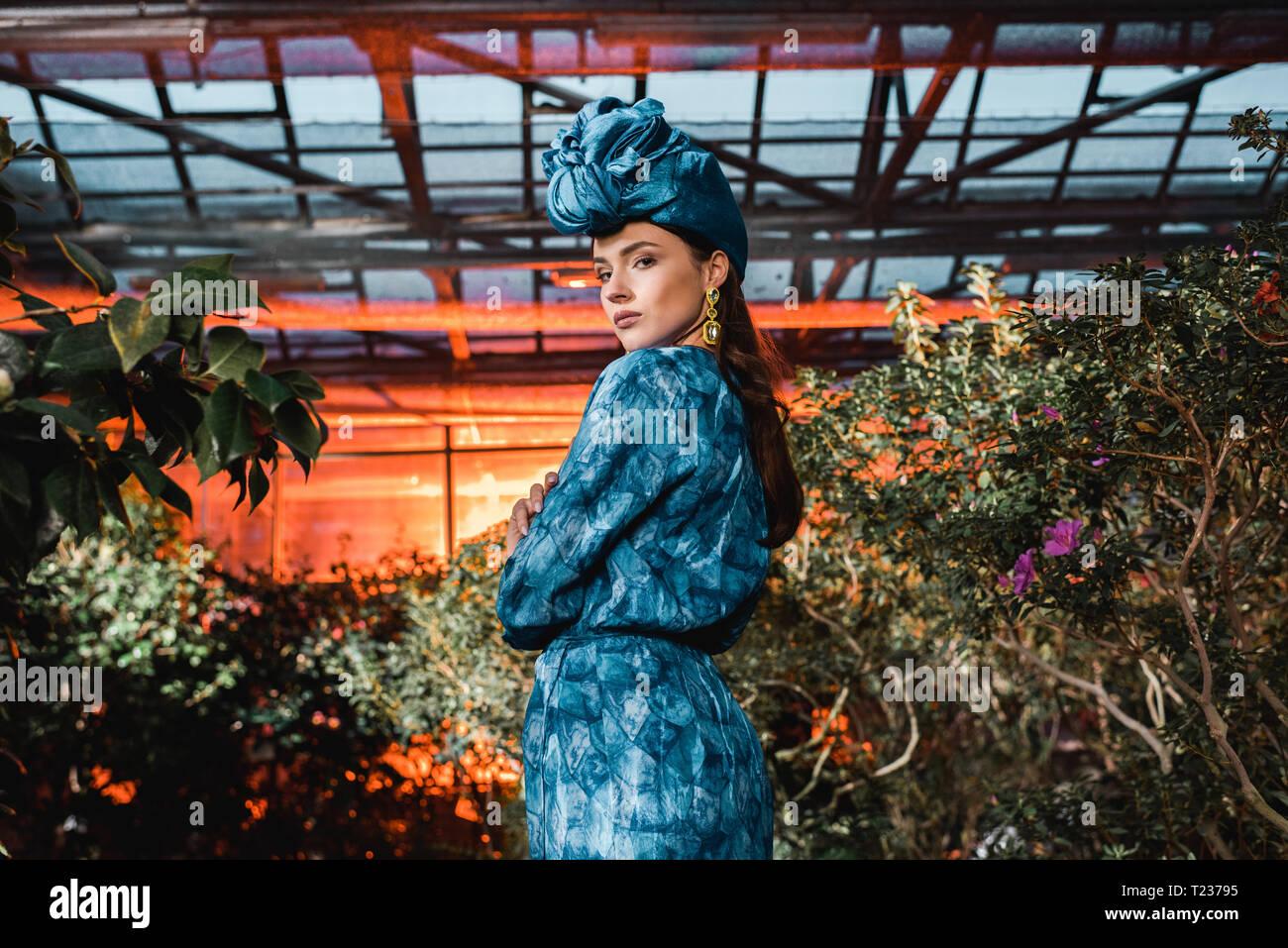 Wunderschöne junge Frau im blauen Kleid in Turban in Orangerie Stockfoto