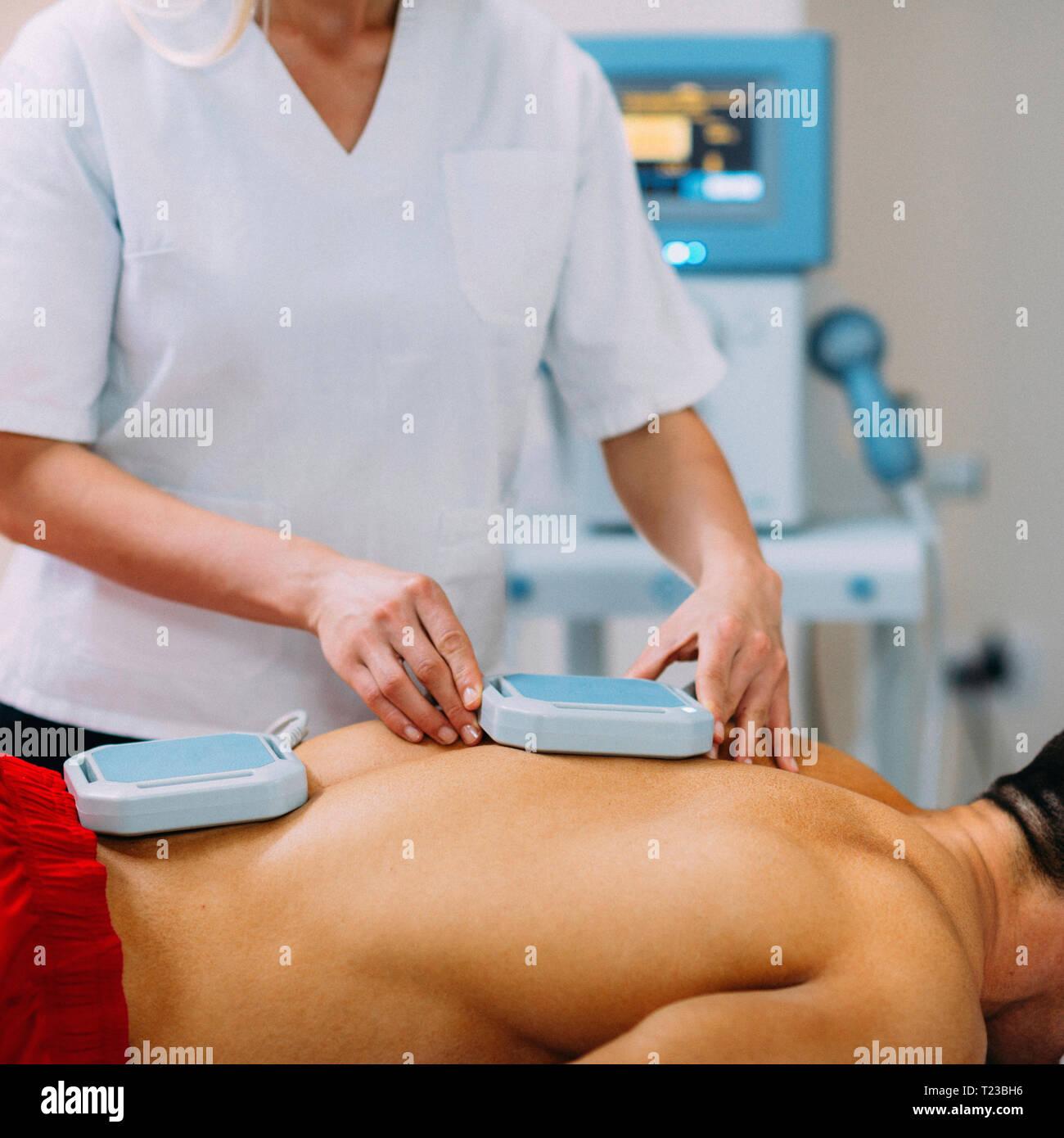 Magnettherapie. Physiotherapeuten Platzierung von Magneten auf Patienten zurück. Stockfoto