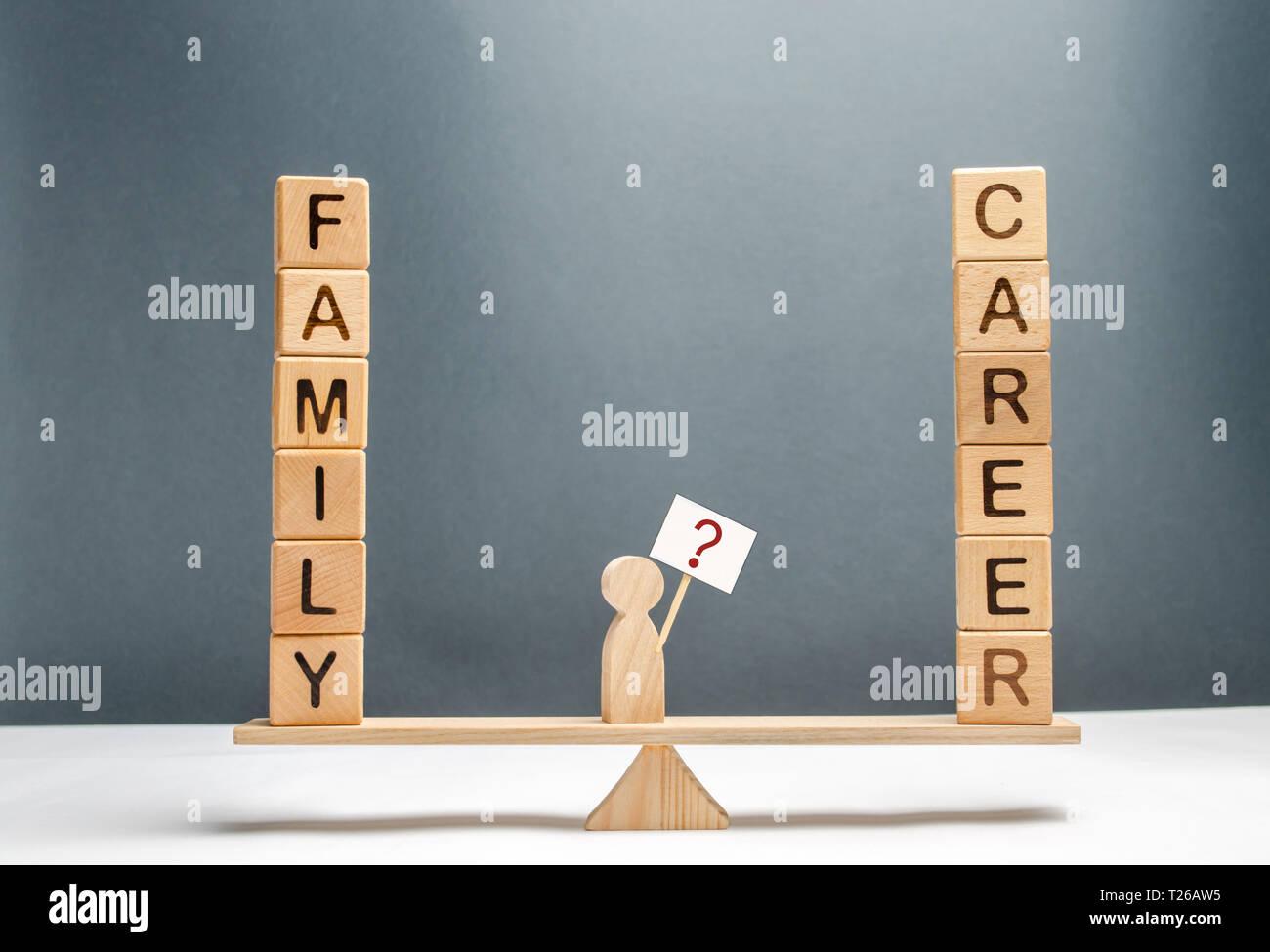 Der Mann auf der Waage mit einem Plakat und ein Zeichen von Fragen. Wahl zwischen Beruf und Familie. Das Konzept der Aufmerksamkeit für die Familie, Promotio Stockfoto