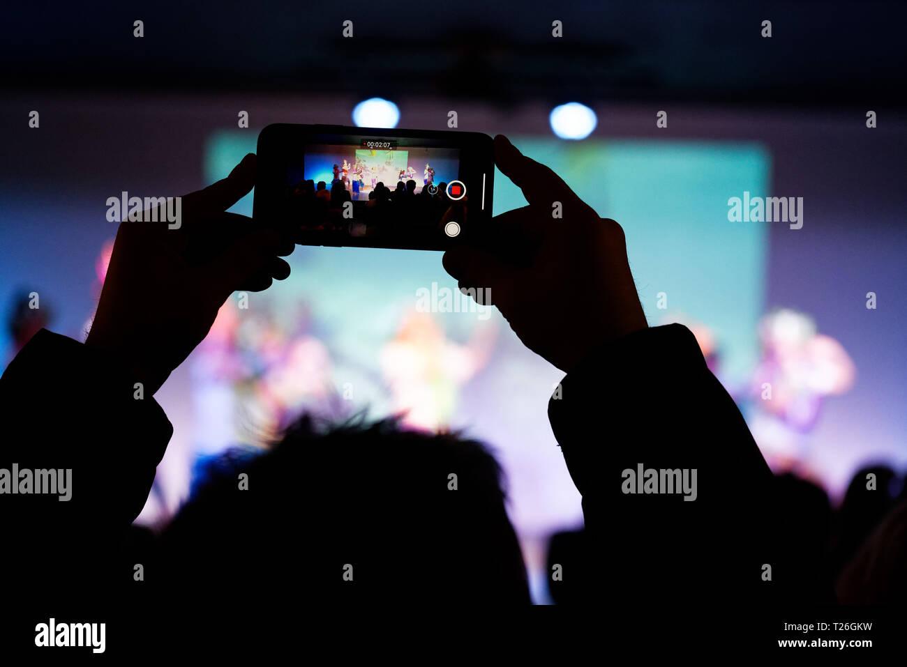 Ein smart phone in der Luft gehalten zu Fotografieren Kinder zeigen Stockbild