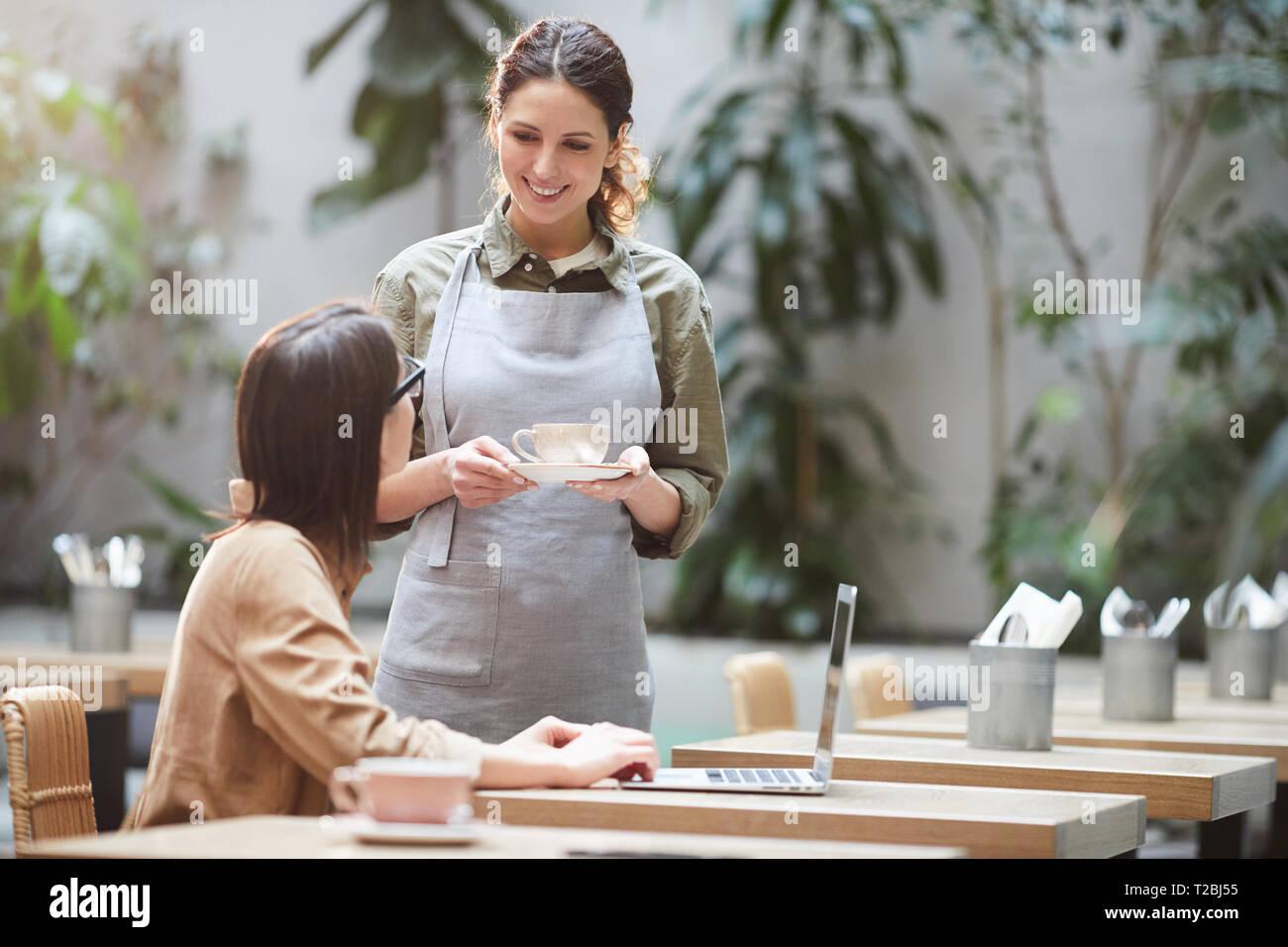 Hübsche Kellnerin die Kaffeetasse zu Client Stockbild