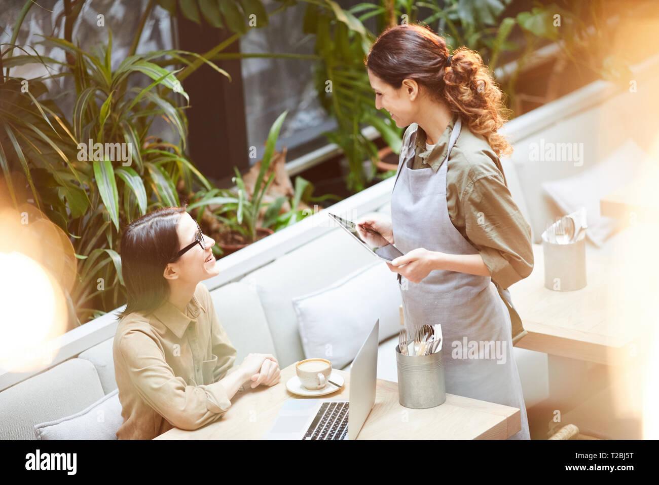 Kellnerin im Gespräch mit jungen Kunden im Cafe Stockbild