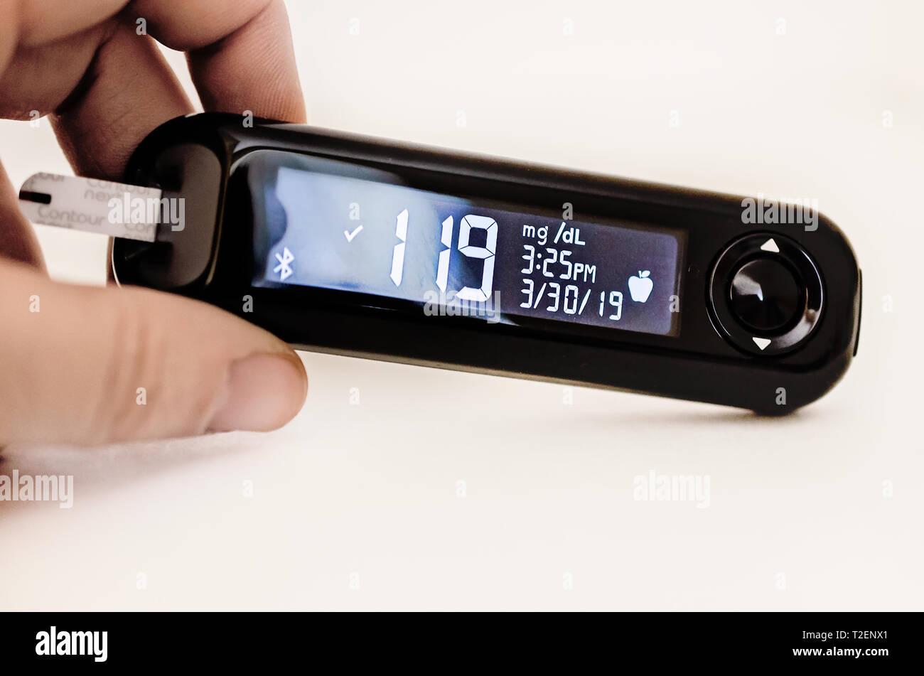 Eine Hand hält eine Kontur nächste Blutzuckermessgerät mit einem hohen Blutzuckerspiegel Messwert von 119 vor einer Mahlzeit. Stockbild