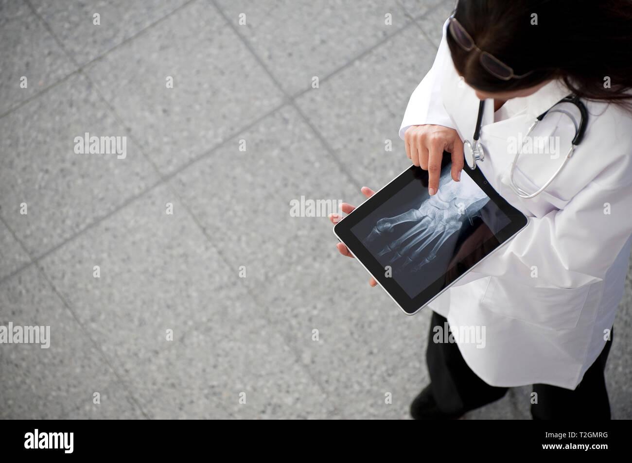 Ärztin suchen an x-ray auf dem ipad tablet Handheld Computer Stockbild