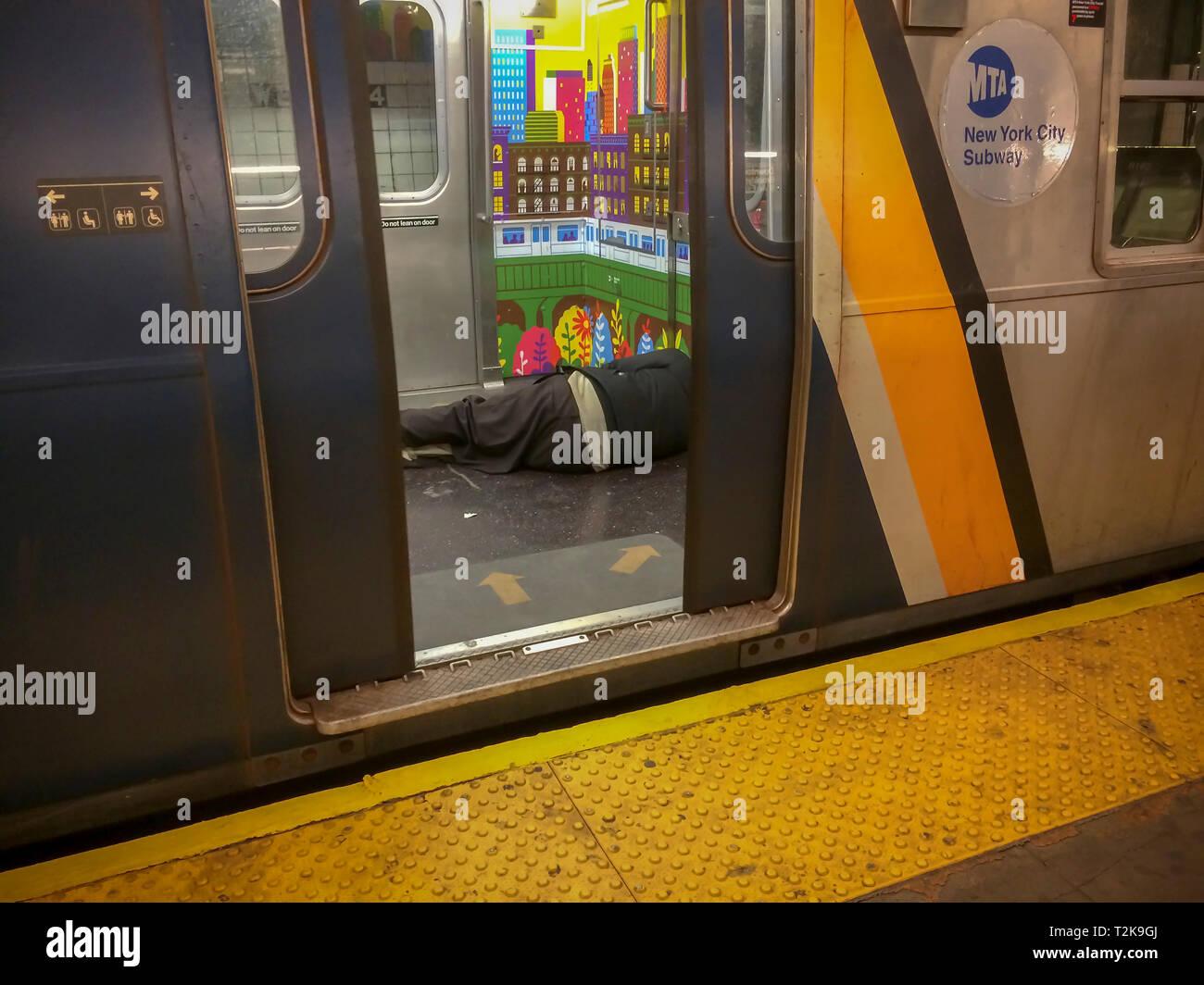 Eine obdachlose Person gesehen wird, schlafen auf dem Boden einer U-Bahn in New York am Dienstag, 26. März 2019. (© Frances M. Roberts) Stockbild