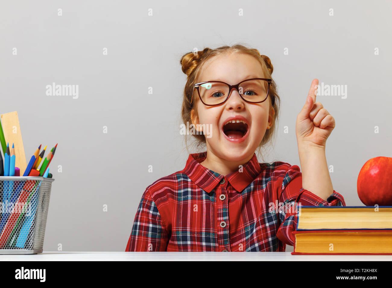 Lustige kleine Vorschule Mädchen in der Brille sitzt am Tisch mit Büchern und Punkte Finger nach oben. Der Begriff der Bildung. Grauer Hintergrund. Stockfoto