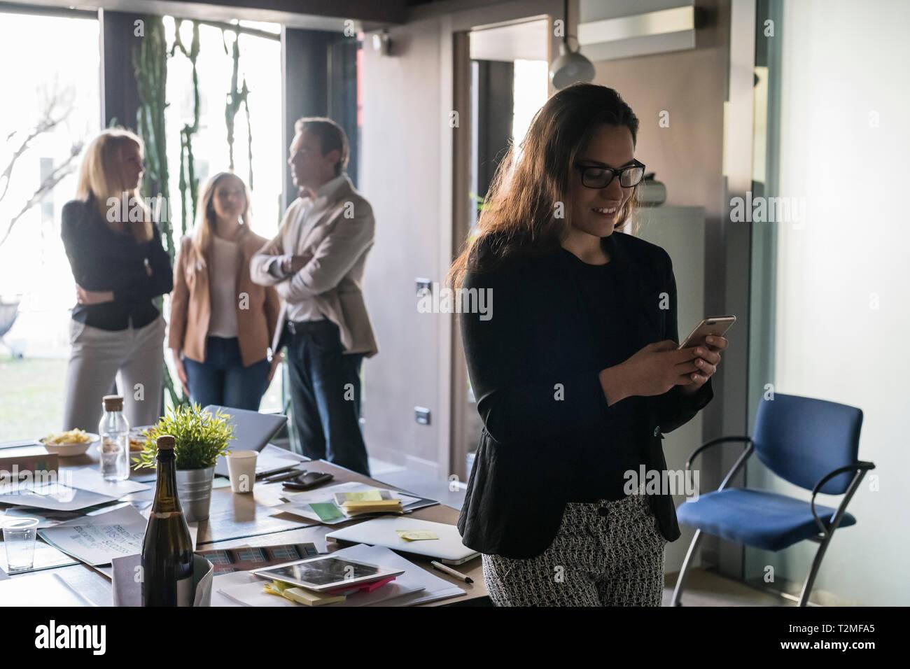 Geschäftsfrau mit im Büro smartphone, Kollegen im Hintergrund Stockfoto