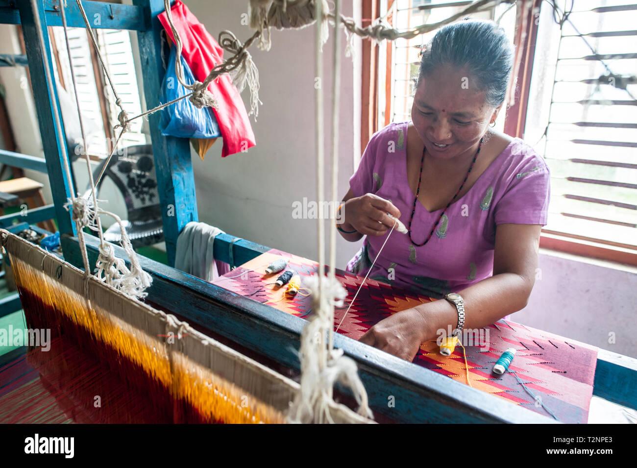 Ein Nepali Frau sticken Seide und Wolle pashmina Schals von Webstuhl, W.F. Nepal, eine nichtstaatliche Organisation, die Beschäftigung von marginalisierten Frauen auf einer gleichberechtigten Basis. Stockbild
