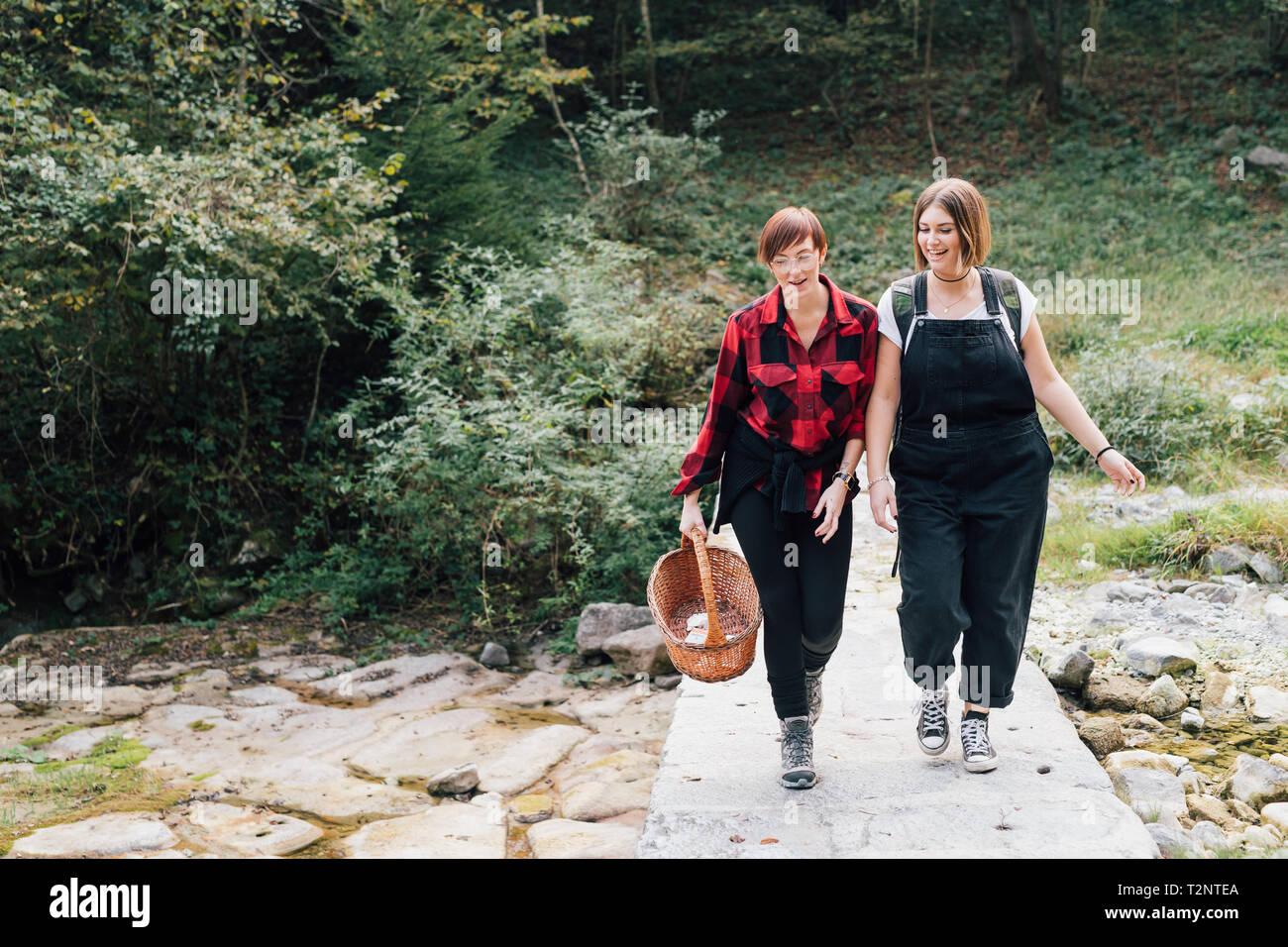 Frauen überschreiten Brücke über trockenes Flussbett, Rezzago, Lombardei, Italien Stockbild