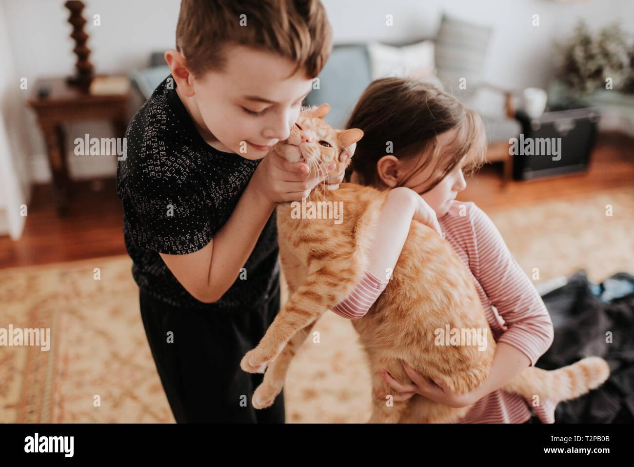 Kinder spielen mit der Katze zu Hause Stockfoto