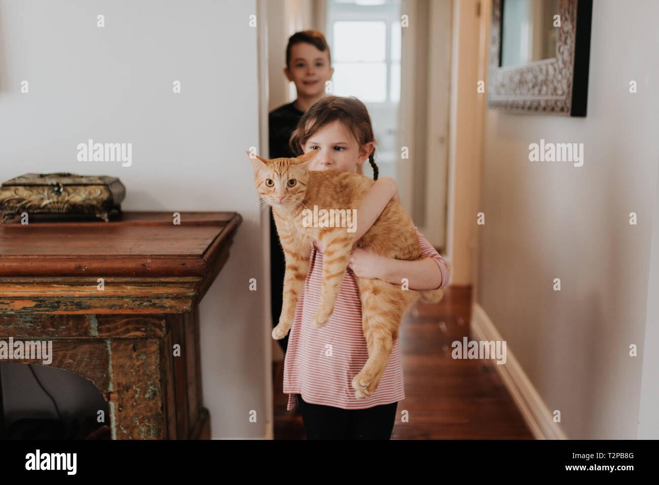 Junge Schwester aufpassen, die Katze zu Hause Stockfoto