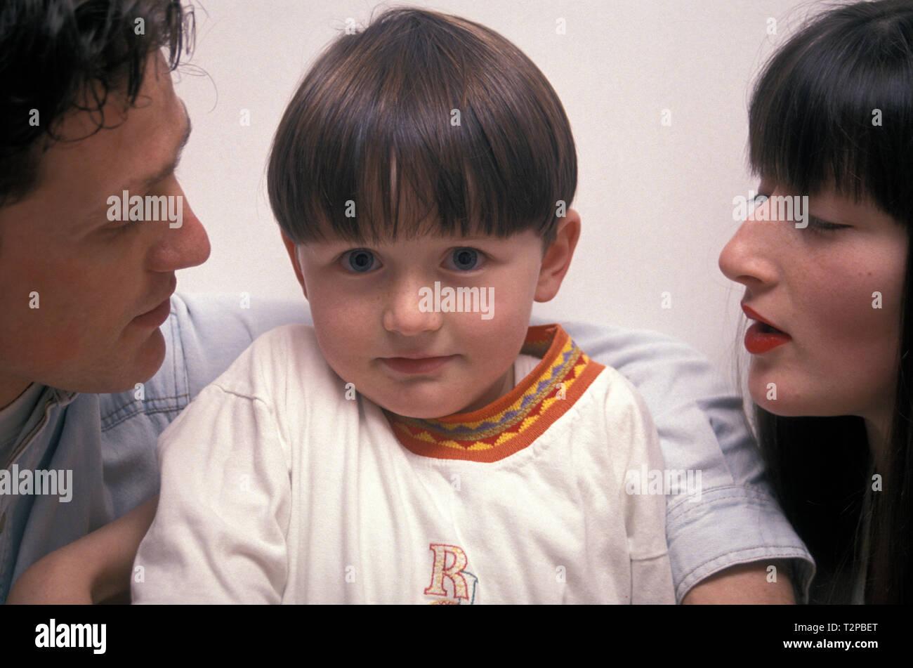 Frechen kleinen Jungen zwischen seinen beiden Eltern Stockbild