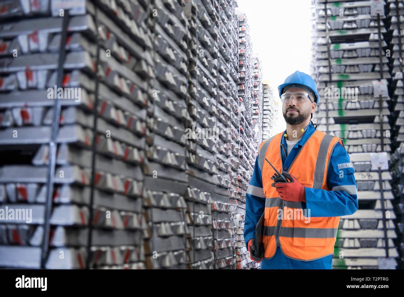Das zusammengesetzte Bild der Arbeiter mit Barren aus Metall Stockbild