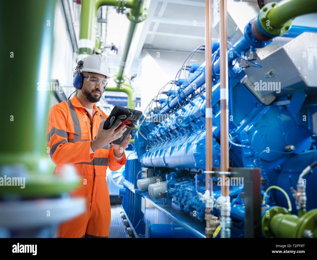 Das zusammengesetzte Bild des Ingenieurs mit digitalen Tablet mit Generator Stockfoto