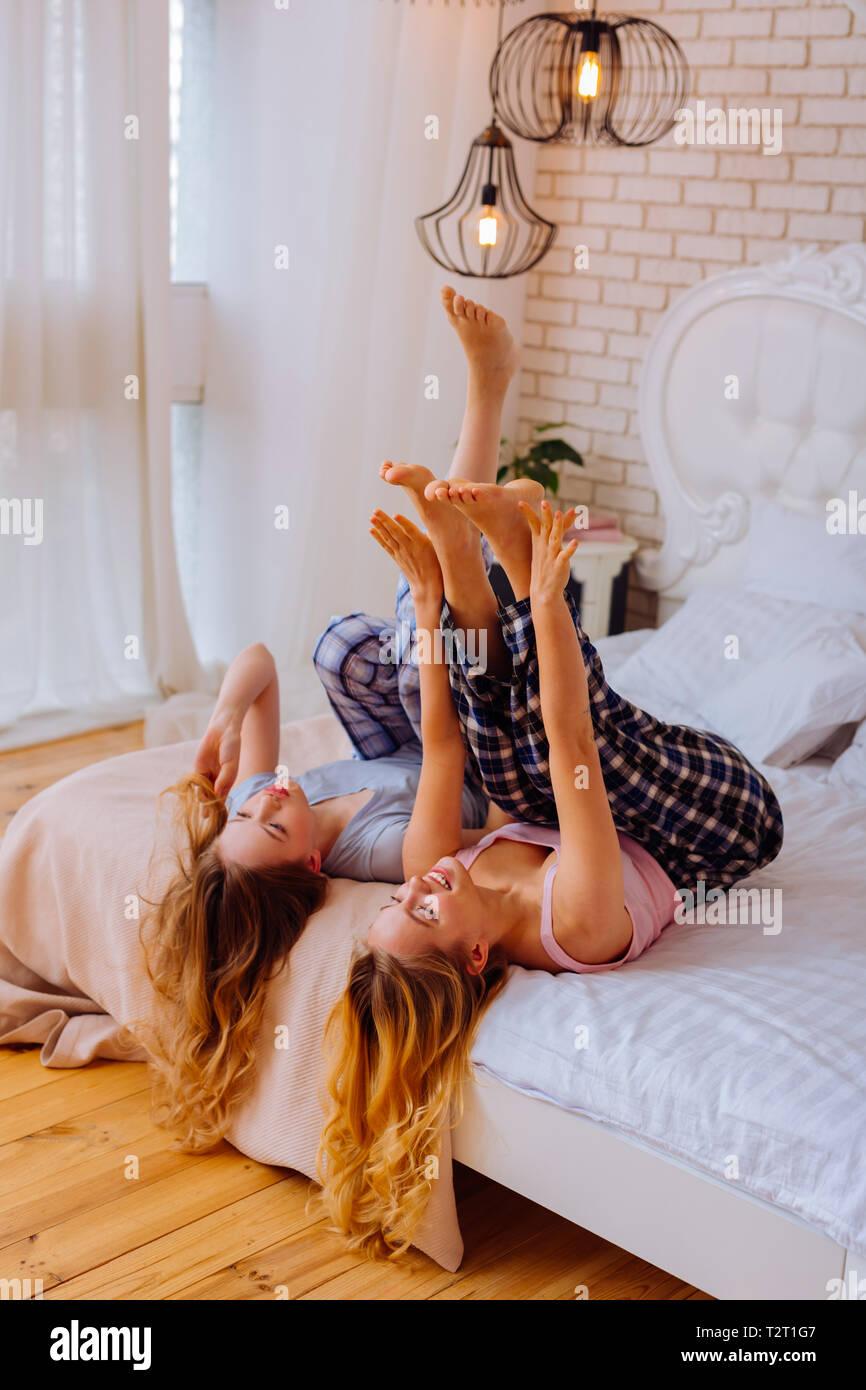 Lockige blonde Haare. Zwei glückliche fröhlichen Schwestern mit dem Lockigen, blonden Haaren Pyjama tragen und Chillen im Bett Stockbild