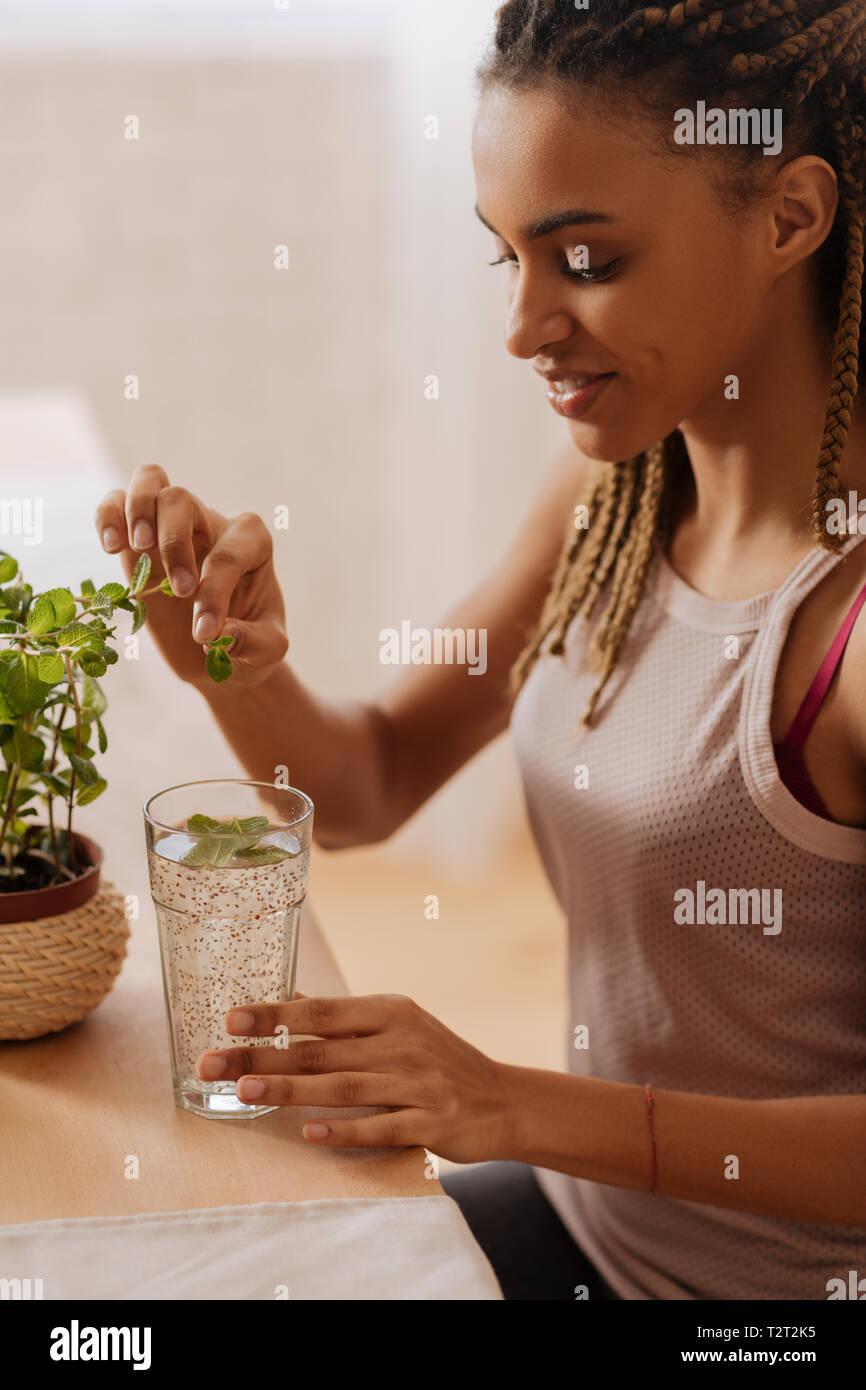 Gesundes Wasser. Junge passende Frau tragen sportliche Kleidung Hinzufügen frische Minze in Wasser Stockbild