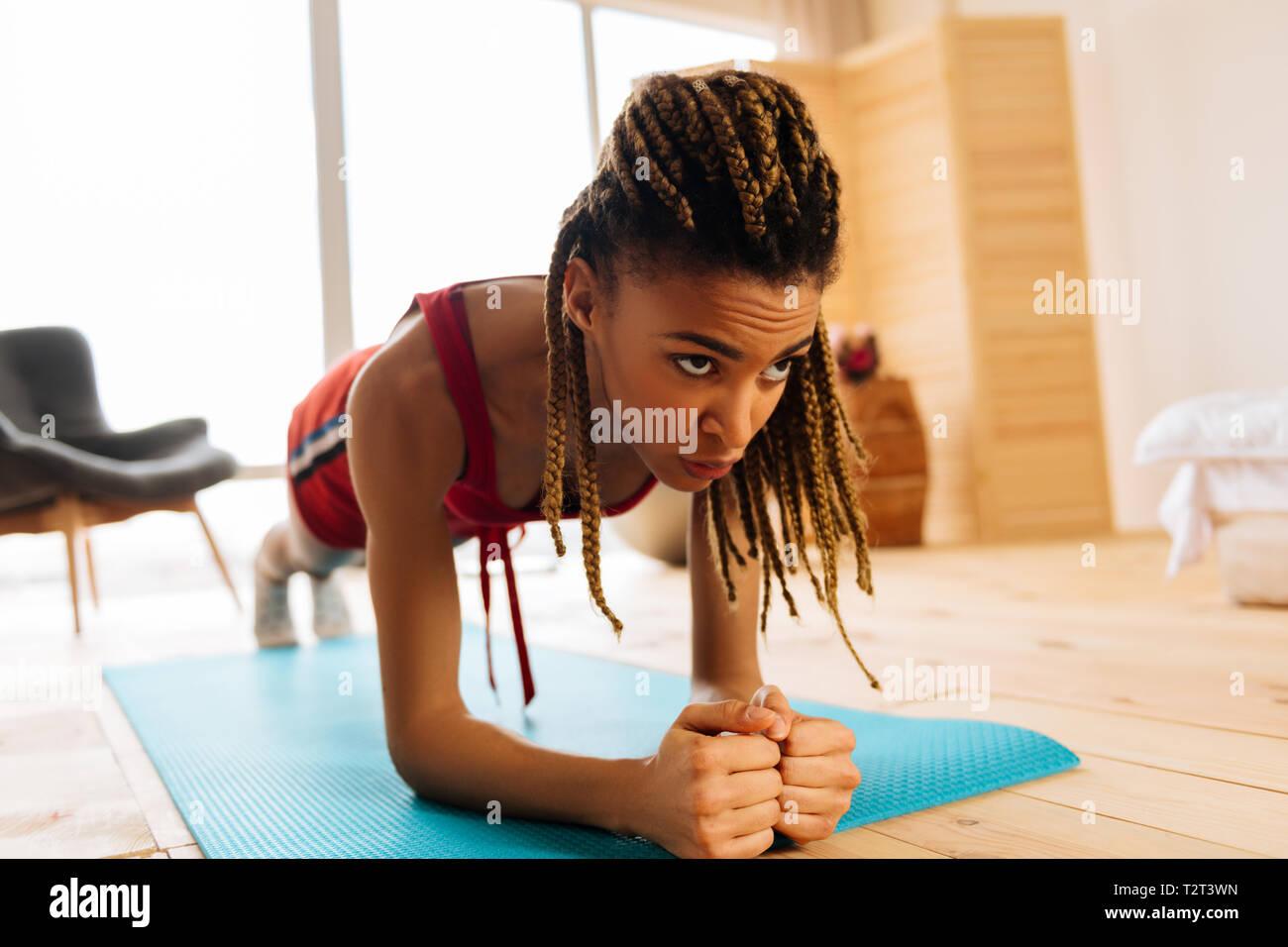 Anstrengend Plank. Dark-eyed Frau mit schönen Zöpfe das Gefühl erschöpft beim Schlichten Workout mit Plank Stockbild