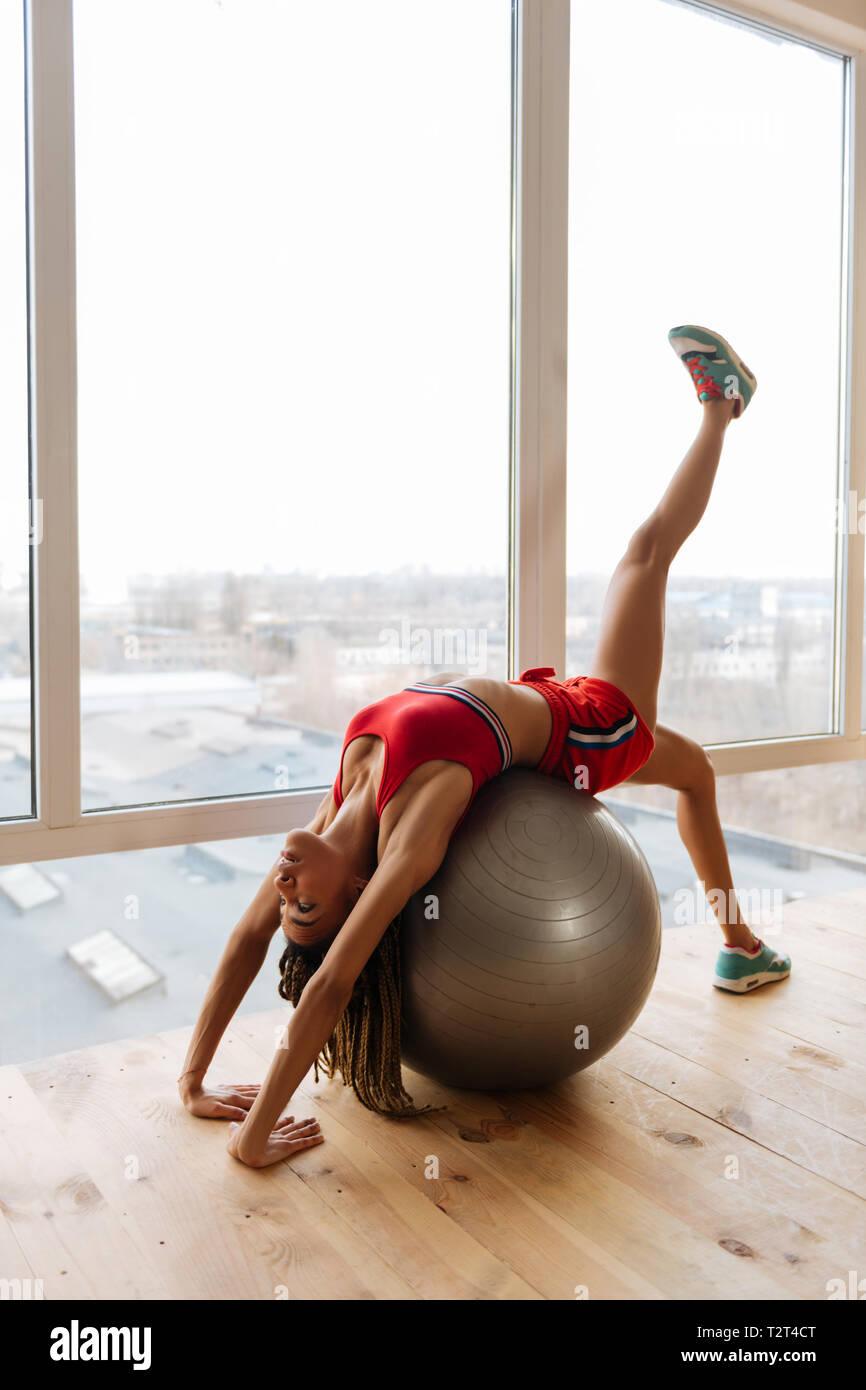 Fitness Ball Zeit. Aktive junge passende Frau tragen sneakers Ausübung auf Fitness Ball zu Hause Stockbild