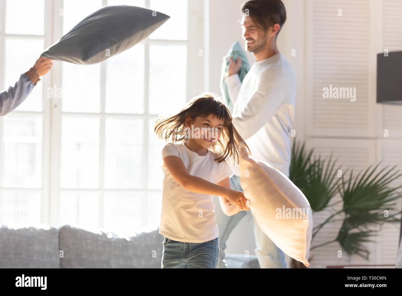 Freundliche Familie und kleine Tochter spielen mit Kissen zu Hause Stockfoto