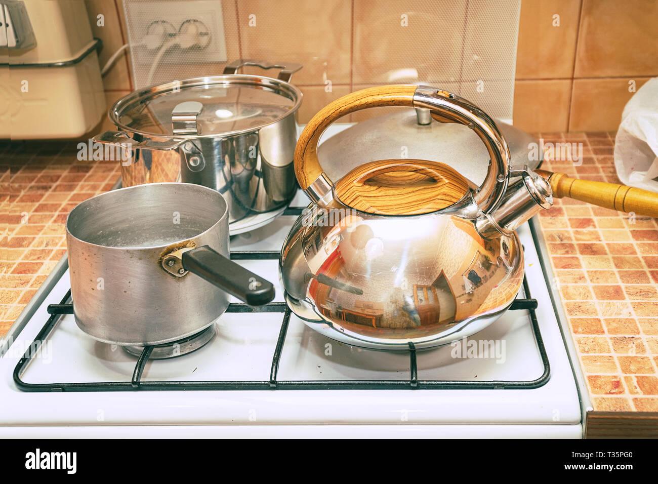 Töpfe, Pfannen und einen Wasserkocher auf dem Gasherd ...