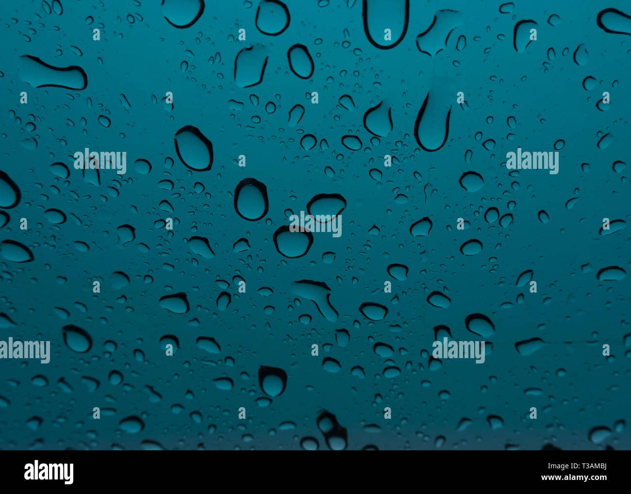 Zu den beruhigenden Klang der Regentropfen prasseln auf die Windschutzscheibe eines Autos hören. Die Kälte macht es noch komfortabler. Stockbild