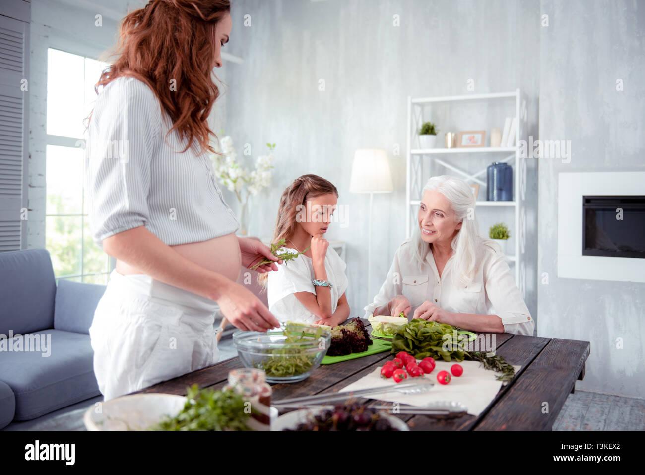 Schwangere dunkelhaarige Frau Abendessen kochen mit Mama und Tochter Stockbild