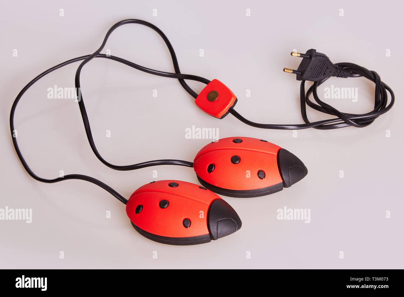 Elektrische uv-schuhtrockner auf weißem Hintergrund. Elektrischer Schuhtrockner in Form von ladybird Stockfoto