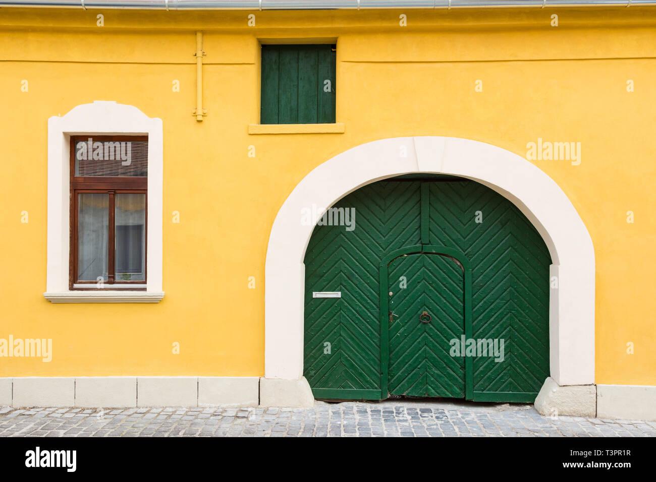 Bevorzugt Gelbe Fassade eines alten Hauses mit Fenster, Dachboden Tür und TX05