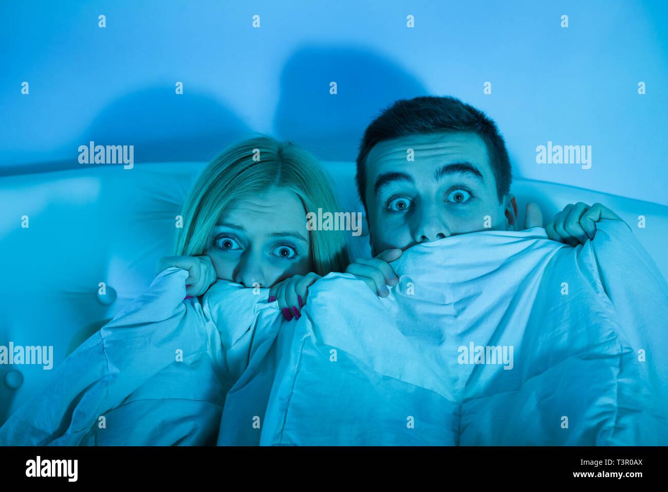 Verängstigte Paar beobachten einen Horrorfilm Stockfoto