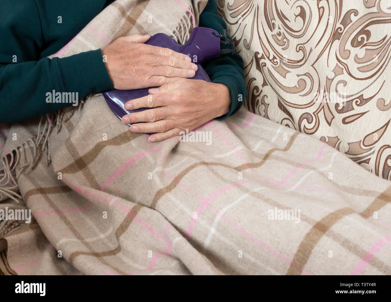Mann auf dem Sofa holding Wärmflasche: Energiekosten, kaltes Wetter, Haushalt Rechnungen, verletzlich Rentner, Menschen Grippe... Konzept Bild Stockbild