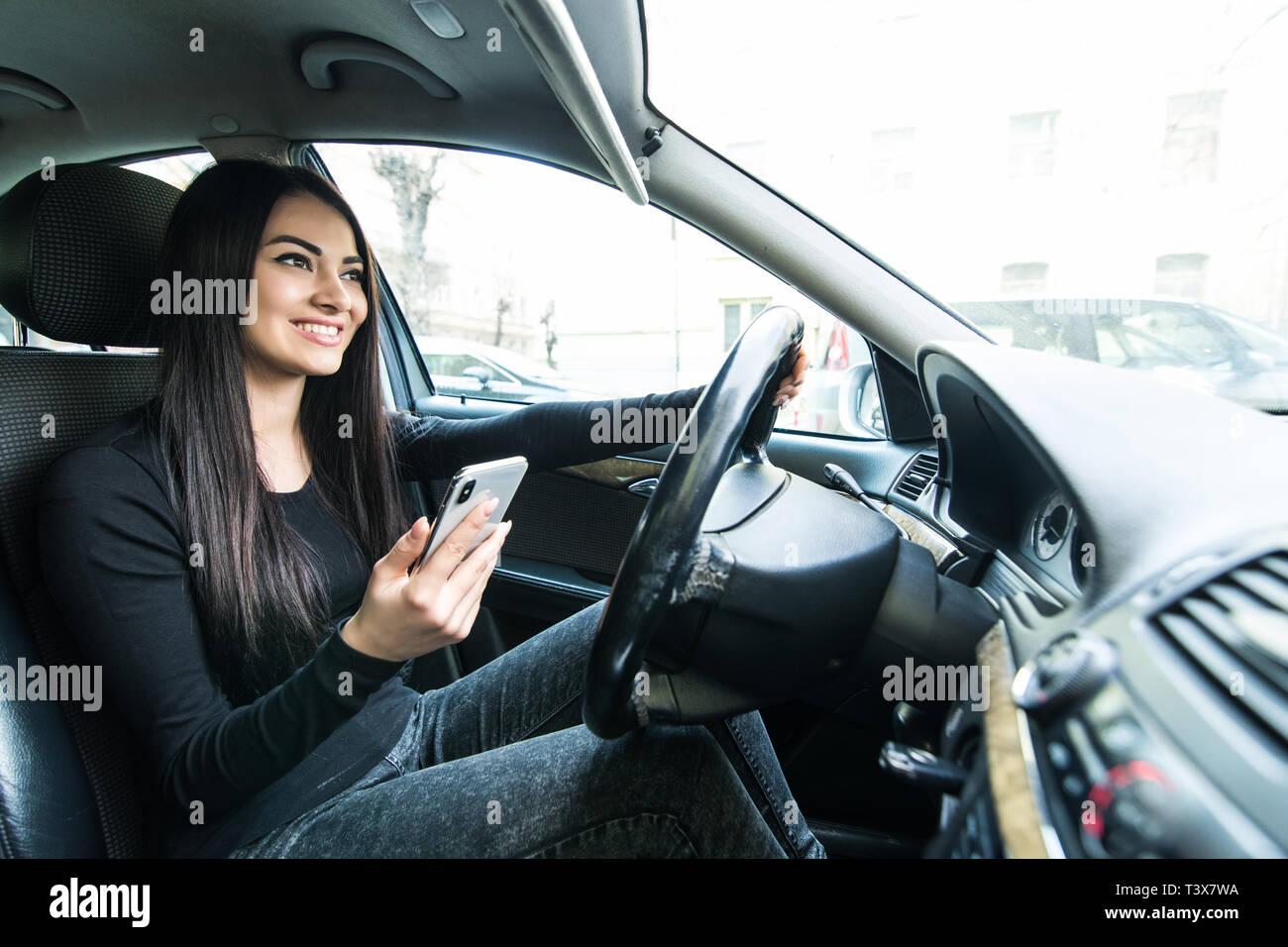 Business Frau im Auto sitzen und über Ihr Smartphone. Mockup Bild mit weiblichen Fahrer- und Verbindungsmenü Stockfoto