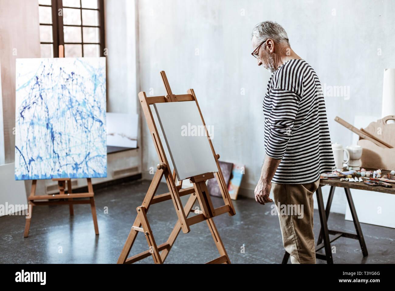 Ohne Inspiration. Bärtige reifen Künstler stand vor der weißen Leinwand ohne Inspiration Stockbild