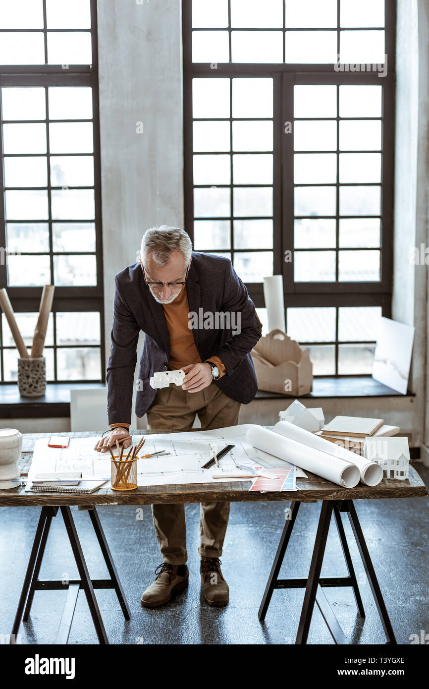 Designer mit Bleistift. Dark-eyed reife Innenarchitekt holding Bleistift während Sketche Stockbild