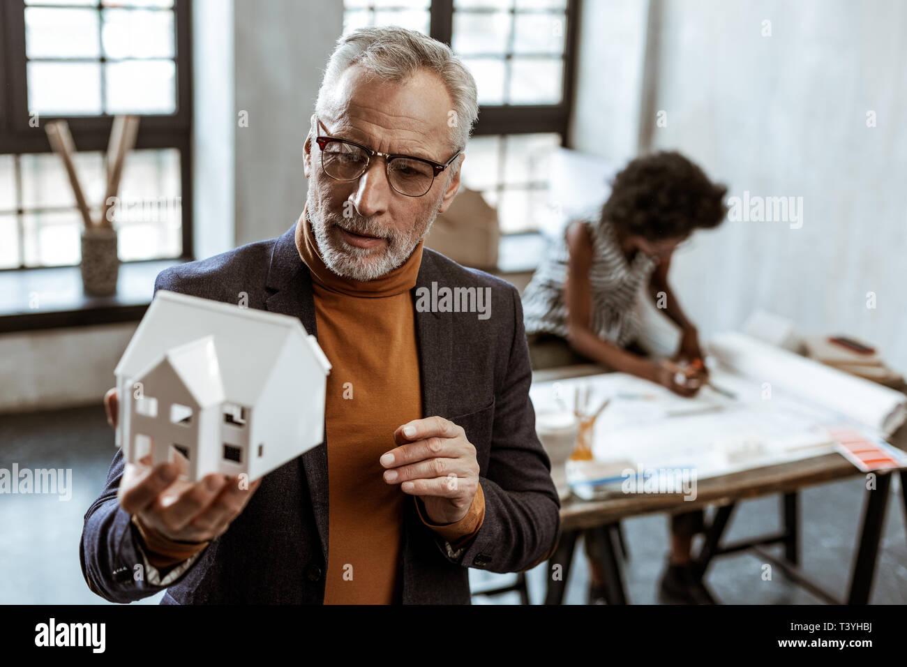 Modell des Hauses. Grau bärtigen Haaren Interior Designer Brillen Holding weiße Modell des Hauses Stockbild