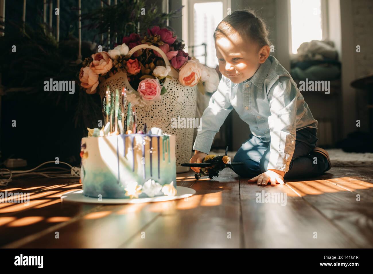 Kleinkind Junge sitzt auf dem Boden in der Nähe der Torte auf dem Hintergrund der Blumen. Stockfoto