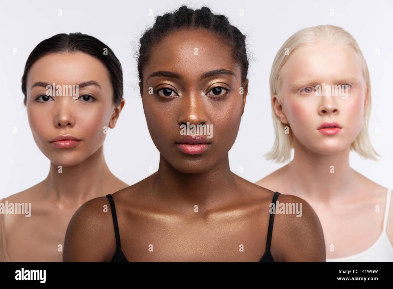 Verschiedene Teint. Drei junge attraktive Frauen mit unterschiedlichen Teint posiert zusammen Stockbild