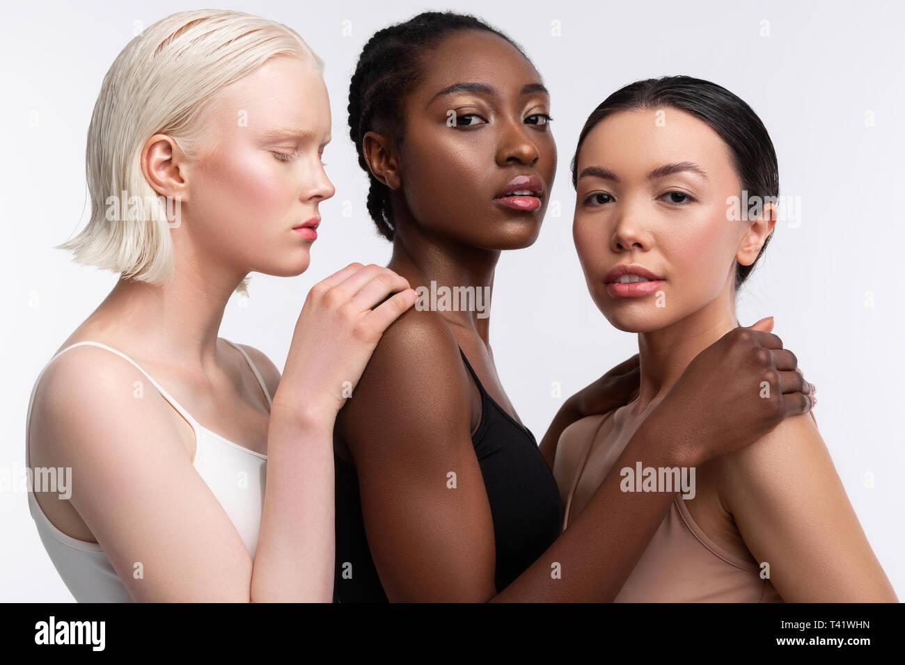 Schultern berühren. Drei Frauen mit unterschiedlichen Haut berühren, Schultern von einander beim Posing Stockbild