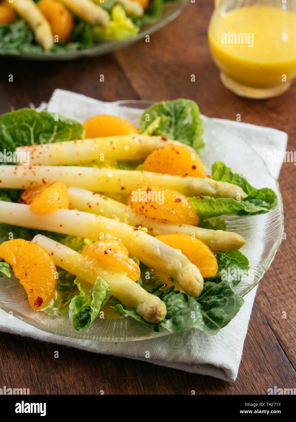 Weißer Spargel auf Salat mit Orangendressing Stockfoto