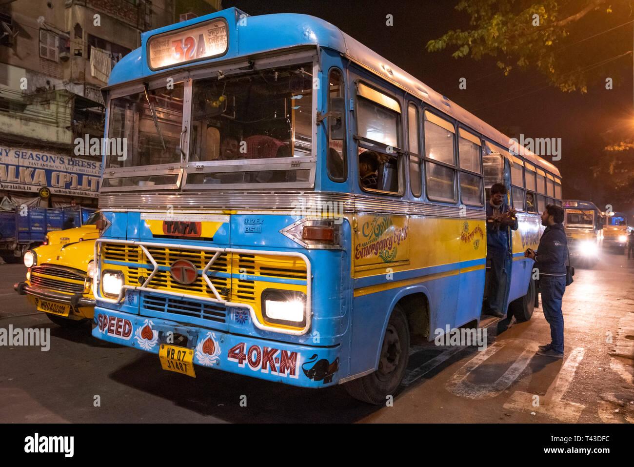 Horizontale Sicht auf einen öffentlichen Bus hinunter die Straße in Kalkutta aka Kalkutta, Indien fahren. Stockfoto