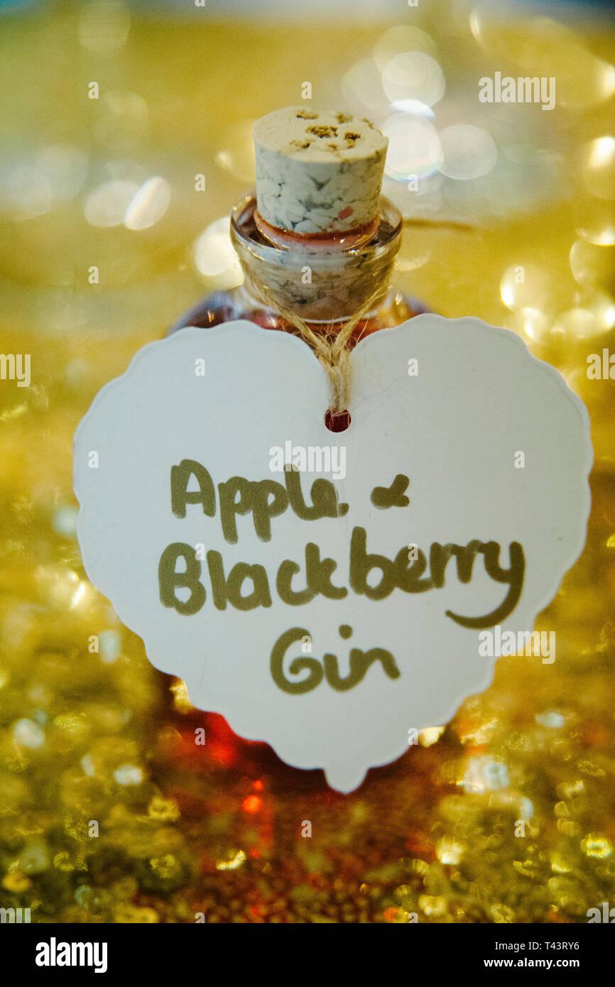Miniatur Flasche hausgemachten Apple und Blackberry Gin mit Gold bokeh Hintergrund. Selbstgemachte Weihnachtsgeschenk Ideen Stockbild