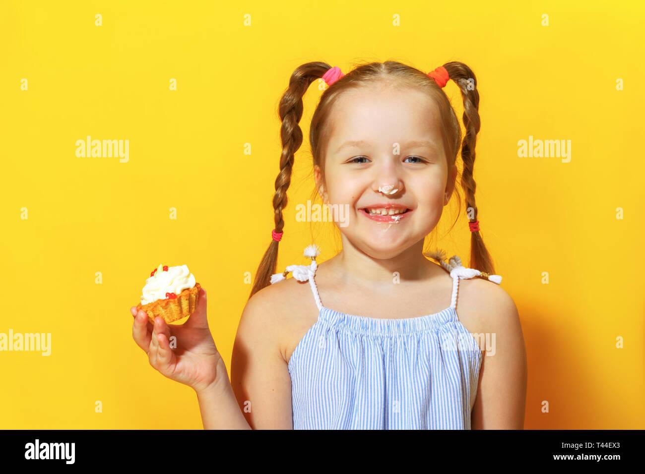Closeup Portrait von Eine fröhliche kleine süße Mädchen auf einem gelben Hintergrund. Das Kind seine Nase mit Sahne bestreichen und mit einem Kuchen in der Hand. Stockbild