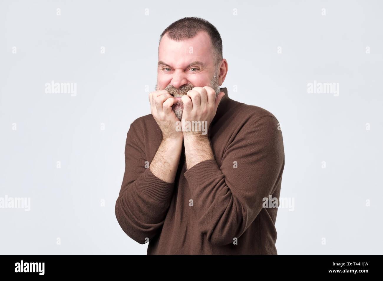Mann mit Bart in braunes Hemd Beißen Nägel in Angst Stockfoto