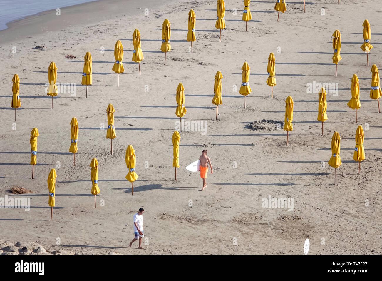 Cartagena Kolumbien Bocagrande Karibik öffentlichen Strand sand Wasser Sonnenschirme gelb Vermietung Hispanic Bewohner Bewohner Mann surfer Stockbild