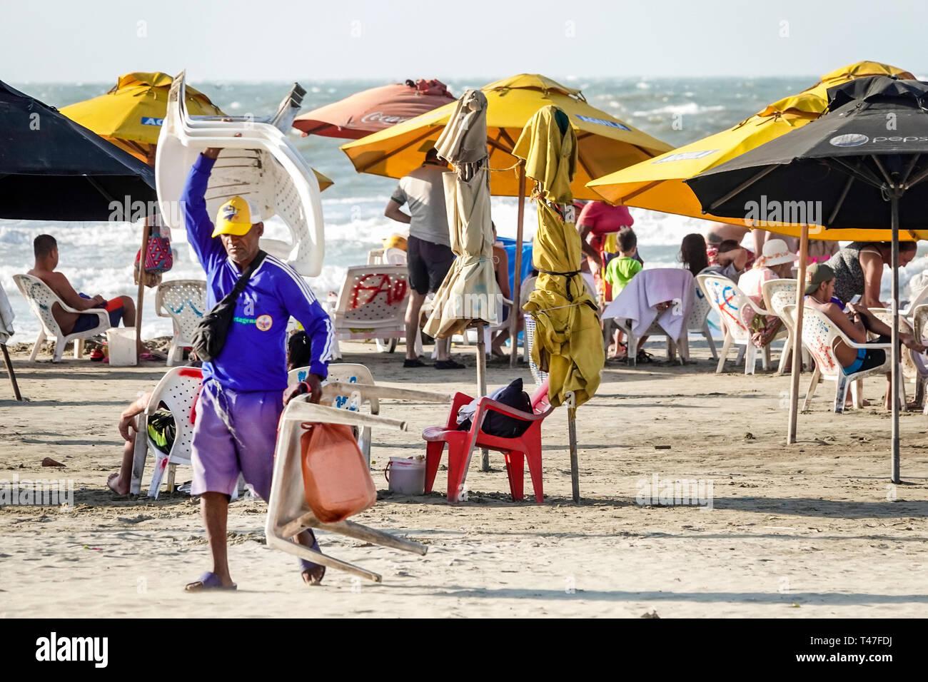 Cartagena Kolumbien El Laguito Hispanic Bewohner Bewohner mann Karibik öffentlichen Strand Sonnenschirme Durchführung Vermietung Stühle sand Stockbild