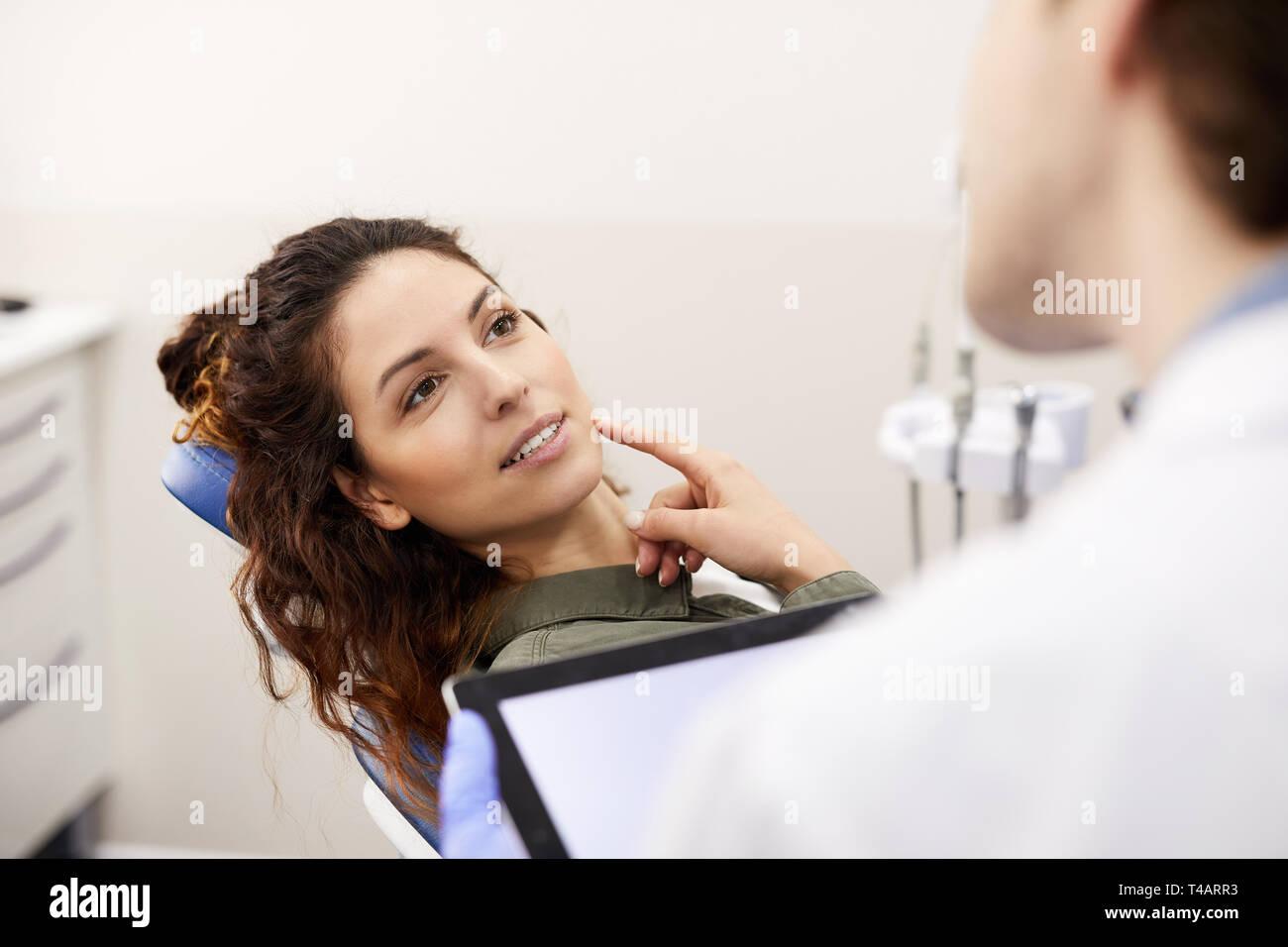 Porträt der schöne junge Frau sitzt im Zahnarztstuhl und Zahn, während die Beratung mit Arzt, kopieren Raum Stockbild